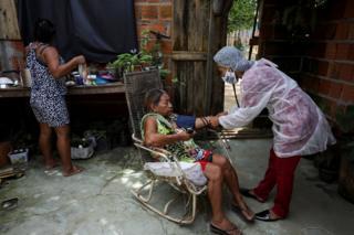 Vanderlecia examines a patient indoors