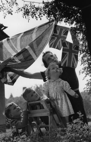 Children help put up bunting and flags on VE Day in London
