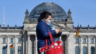 Northern Ireland Woman walks past Reichstag wearing a mask