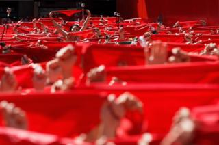 Revellers hold up their red handkerchiefs during the opening day of the San Fermin Running of the Bulls fiesta in Pamplona, Spain