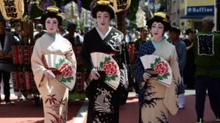 Women in kimono pose for a photograph in the street of Asakusa during Sanja festival on May 19, 2019
