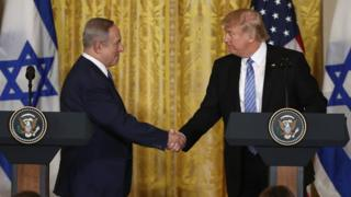 US President Donald Trump (R) and Israel Prime Minister Benjamin Netanyahu (L) shake hands during a joint news conference at the East Room of the White House