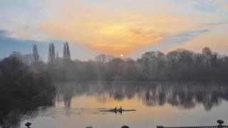 Rowers on a lake in Twickenham as the sun rises