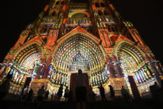 People gather outside Amiens Cathedral in France, which is lit up at night