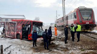 Police officers at the scene where a train ploughed through a bus in southern Serbia, 21 December 2018