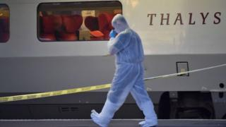 Forensic investigator walk next to the Thalys train after a foiled attack