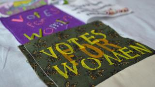 """Votes For Women"" patch on Girl Gang Manchester's banner"