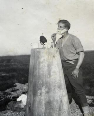 Man shaving on trig pillar