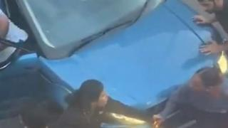 Woman trapped between cars