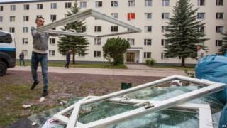 Refugee piles up damaged windows in Suhl (20 Aug)