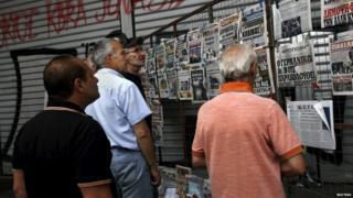 People read newspaper headlines in Athens on 27 June