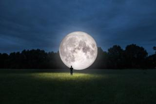 мужчина и изорбажение Луны на поляне