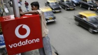 A worker adjusting a Vodafone sign in India