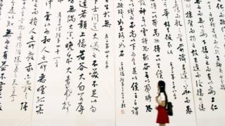 Một khách tham quan xem tác phẩm thư pháp lớn nhất thế giới tại một triển lãm tại Nam Kinh.
