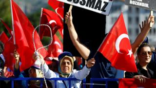 A crowd waves Turkish flags and brandishes a noose outside the court