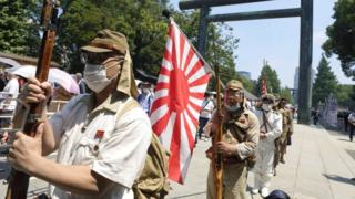 People wearing Japanese Imperial army and navy costumes hold a rising sun flag as they pay tribute to the war dead at Yasukuni Shrine
