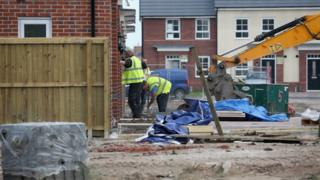 Construction workers build new houses on a housing development in England