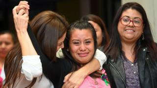 Salvadorean rape victim Evelyn Hernandez (C) celebrates with her lawyers
