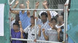 Asylum seekers look through a fence at the Manus Island detention centre in Papua New Guinea in 2014