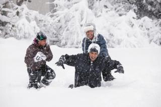 Obama plays in the snow with his children