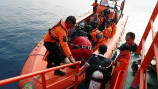 Divers board a small boat off Jakarta