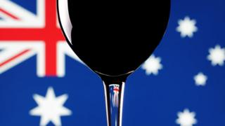 A wine glass in front of the Australian flag