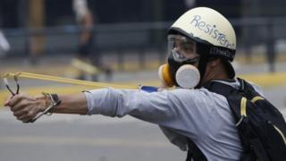 A protester fires a sling-shot during violent clashed in Venezuela
