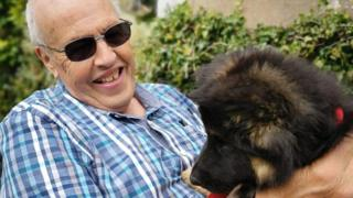 Bernard Lawrence pictured laughing with a pet dog