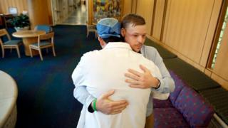 In this Jan. 25, 2017, photo, face transplant recipient Andy Sandness is hugged by Dr. Samir Mardini, who performed his surgery. You can see light scarring under his eyes and across his temples.