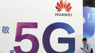 A man walking past a Huawei 5G sign