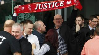 "Hillsborough campaigners holding a Liverpool scarf that reads ""justice""."
