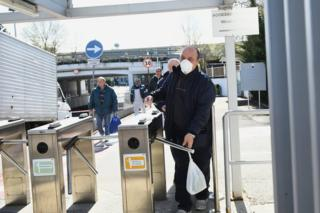 A man walks through a turnstile whilst wearing a face mask