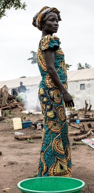 A South Sudanese woman standing in a colourful dress - Saturday 11 May
