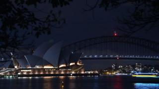 Sydney Harbour Bridge and the Opera House are plunged into darkness for the Earth Hour environmental campaign on March 24, 2018.