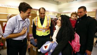 トロント・ピアソン空港でシリア難民たちを歓迎するトルドー首相(左)