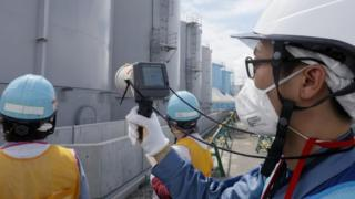 A staff member of the Tokyo Electric Power Company measures radiation levels at the Fukushima nuclear power plant