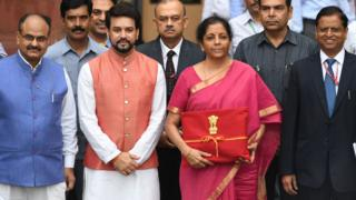 Indian Finance Minister Nirmala Sitharaman (2R) with Minister of State for Finance Anurag Thakur (2L) looks on as she poses for a picture with her staff before leaving the Indian Finance Ministry for Parliament House to table the General Budget 2019-20 in New Delhi on July 5, 2019.