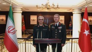 رئيس أركان الجيش الإيراني ونظيره التركي يقفان وعلى جانب كل منهما علم بلاده