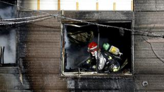 A firefighter at the burnt-out elderly home