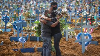 Mourners wearing protective masks at a mass burial of coronavirus victims in Manaus, Brazil - 19 May 2020