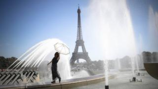 A woman in a summer dress holds a parasol over her head as the fountains in front of the Eiffel Tower spray her with a fine mist