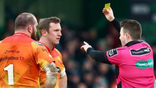 Referee Ben Whitehouse hands a yellow card to Scarlets prop Phil John