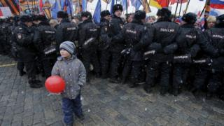 """Boy stands in front of Russian police officers during festive concert marking second anniversary of Russia""""s annexation of Crimea in central Moscow"""