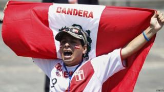 A supporter holds a Peruvian flag after knowing the final ruling court decision of a decades-old maritime dispute between Peru and Chile, at the Government Palace in Lima