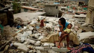 A mother and her daughter sit on the spot where their home collapsed during the earthquake, February 26 2010 in Port-au-Prince, Haiti.