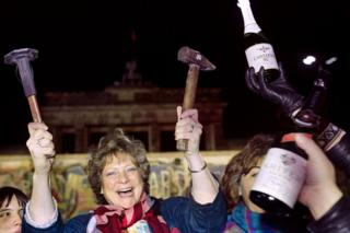 A berliner holds up a hammer and a chisel early on November 15, 1989 in front of the wall at the Brandebourg Gate partly visible behind it as a crowd of people demonstrated for the destruction of the wall for a passage way between the East and the West near the monument.