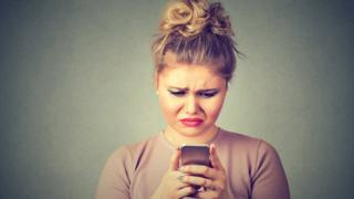 Woman looking unhappily at mobile phone