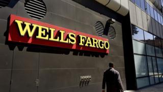 Un hombre camina frente a una sucursal de Wells Fargo.