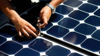 Hands installing solar panels