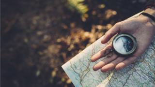 Mano con brújula y mapa